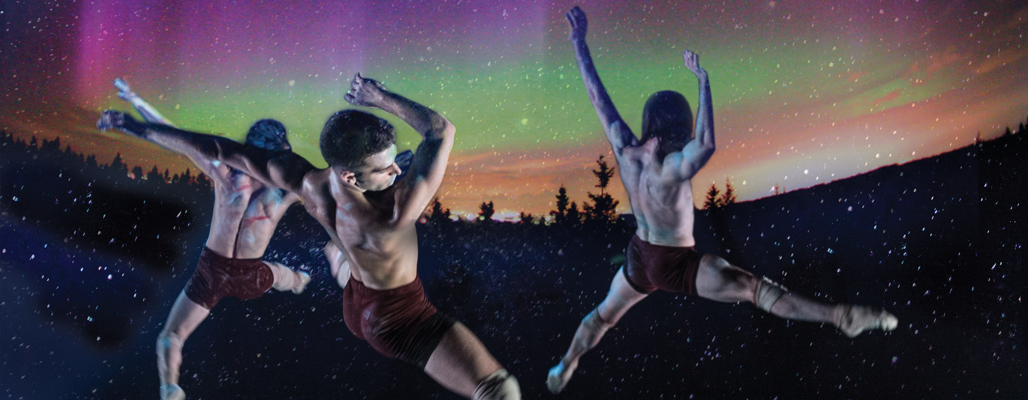 Indigenous Canadian dancers leap against the sparkling backdrop of the Northern Lights.